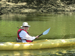 Senior citizen in lifejacket canoeing