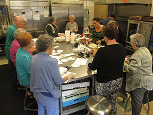 Senior citizens cooking in kitchen