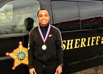 man standing in front of Sheriff van wearing a medal