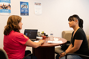 A Family Justice Center employee and a client sitting at a table.