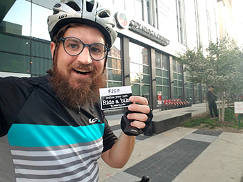 man holding a card wearing a bike helmet