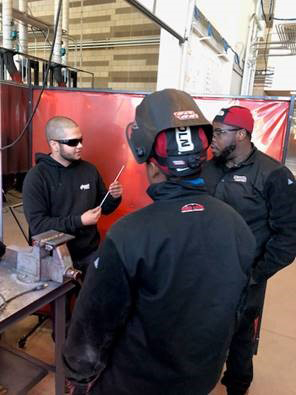 man shows welding peice to two welding students