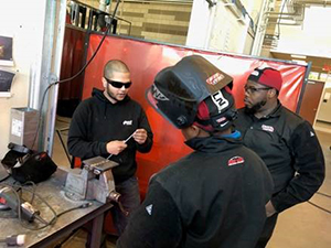 man shows welding piece to two welding students