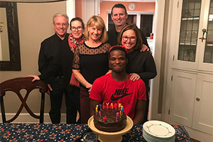 A group of 6 people standing in front of a birthday cake
