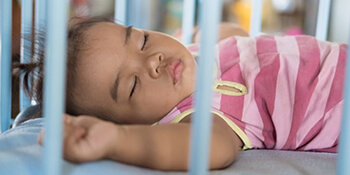 Baby sleeping in crib on back