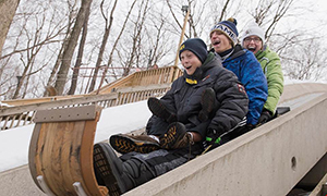 a family riding a toboggan