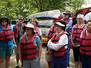 Group of seniors with lifejackets on and canoes in background