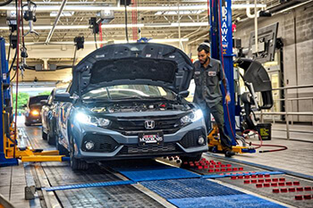 Honda with hood open in assembly line.