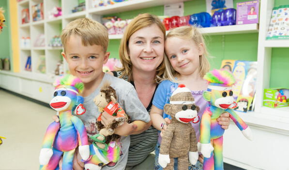 Woman smiling with 2 children holding stuffed animals