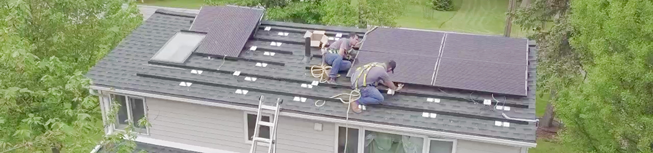 workers installing solar panels to house