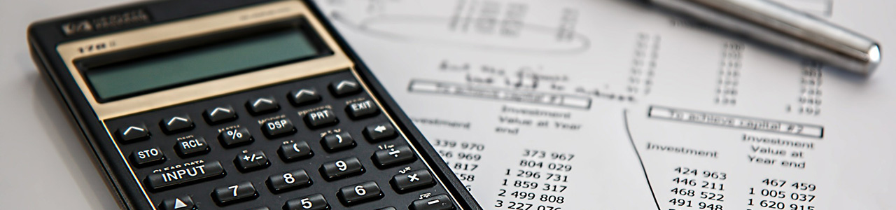 calculator and pen on top of tax papers